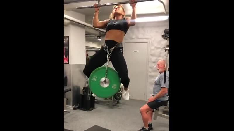 Девушка подтягивается с доп. весом в 20 кг